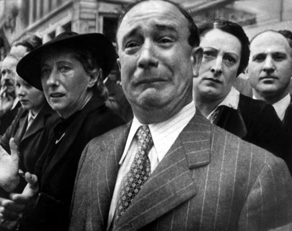 14 iunie 1940; un francez plânge, în timp ce trupele germane mărṣăluiesc la Paris; http://commons.wikimedia.org