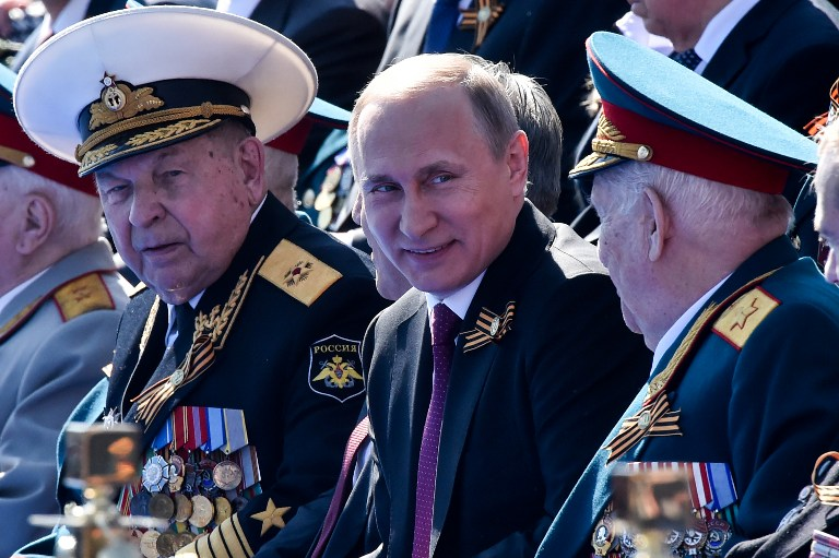 Russian President Vladimir Putin (C) attends the Victory Day military parade at Red Square in Moscow on May 9, 2016. Russia marks the 71st anniversary of the Soviet Union's victory over Nazi Germany in World War II. / AFP PHOTO / KIRILL KUDRYAVTSEV