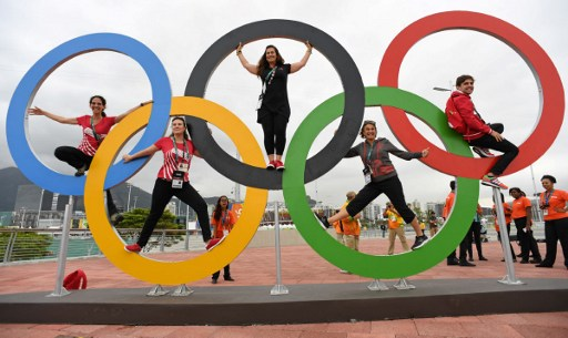 People pose with the Olympic rings at the Olympic Park in Rio de Janeiro, on August 3, 2016, ahead of the 2016 Rio Olympic Games. / AFP PHOTO / Kirill KUDRYAVTSEV