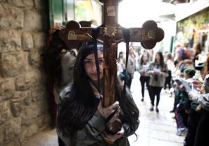 A Palestinian Catholic worshiper holds a cross during the Good Friday procession along the Via Dolorosa (Way of Suffering) on April 3, 2015 in Jerusalem's Old City. Thousands of Christian pilgrims take part in processions along the route where according to tradition Jesus Christ carried the cross during his last days. AFP PHOTO / THOMAS COEX / AFP PHOTO / THOMAS COEX