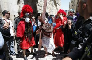 "Christian pilgrims reenact the crucifixion of Jesus Christ along the path where Jesus walked, now known as the ""Via Dolorosa"", or the ""Way of Suffering"", on Good Friday in Jerusalem's Old City on April 18, 2014. Christian pilgrims mark the anniversary every year by walking from the Garden of Gethsemane on the Mount of Olives to the Church of the Holy Sepulchre in the middle of the Old City, an ancient sprawling shrine which Orthodox and Catholic Christians believe was built on the original site of the crucifixion and burial of Jesus.  AFP PHOTO / THOMAS COEX / AFP PHOTO / THOMAS COEX"
