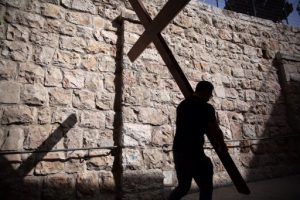 A Catholic pilgrim carries a wooden cross along the Via Dolorosa (Way of Suffering) in Jerusalem's Old City during the Good Friday procession on March 25, 2016.  Many Christian pilgrims took part in processions along the route where according to tradition Jesus Christ carried the cross during his last days.   / AFP PHOTO / Gali Tibbon