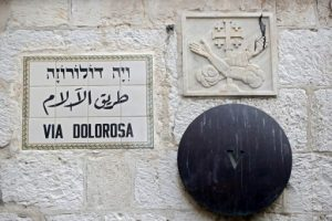 A picture taken on April 1, 2017 shows a street name sign bearing the name of the famous Via Dolorosa street in English, Arabic and Hebrew writing, on a wall in the street in Jerusalem's Old City, near the 5th station, where according to Christian belief, Jesus walked with the cross before being crucified.  / AFP PHOTO / THOMAS COEX
