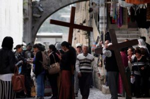 Christian pilgrims carry a wooden cross along the Via Dolorosa (Way of Suffering) in Jerusalem's Old City during the Good Friday procession on March 25, 2016. Many Christian pilgrims took part in processions along the route where according to tradition Jesus Christ carried the cross during his last days. / AFP PHOTO / THOMAS COEX