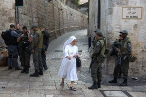 A nun walks past Israeli police as they stand guard in the Via Dolorosa street in the Old City of Jerusalem on October 4, 2015. Israel took a rare and drastic step of barring Palestinians from the Old City as tensions mounted following attacks that killed two Israelis and wounded a child. The restrictions will be in place for two days, with only Israelis, tourists, residents of the area, business owners and students allowed.  AFP PHOTO / MENAHEM KAHANA / AFP PHOTO / MENAHEM KAHANA