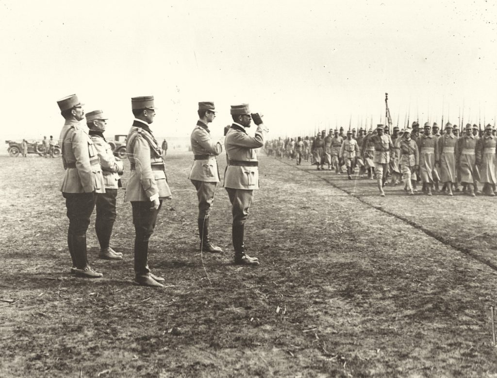 Regele Ferdinand, gen. Eremia Grigorescu şi prinţul Carol pe frontul refacerii (în Moldova) dând onorul unui regiment de jandarmi; sursa: ro.wikipedia.com