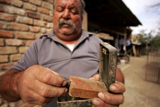 Miroslav Kusanic tine in maini minele antipersonal gasite in gradina sa. AFP PHOTO / ELVIR TABAKOVIC /