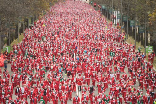 People dressed in Santa Claus costumes participate in the six kilometre charity race to raise funds for multiple sclerosis research, in Madrid on December 17, 2016.   / AFP PHOTO / CURTO DE LA TORRE