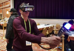 Exhibitor Mark Gonnella of Lenovo demonstrates the Lenovo Jedi Challenges at the ShowStoppers exhibition on the sidelines of CES 2018 in Las Vegas on January 9, 2018. The smartphone powered augmented reality headset comes with lightsaber and location beacon. / AFP PHOTO / Mandel Ngan