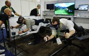 An exhibitor (R) demonstrates the ICAROS virtual reality exercise machine at the Sands convention hall during CES 2018 in Las Vegas on January 9, 2018. The machines allows a user to fly through a virtual environment while exercising. / AFP PHOTO / MANDEL NGAN