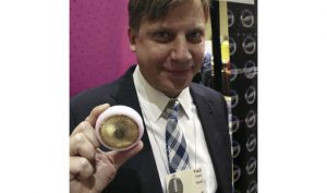 """Foreo chief executive Paul Peros, at the International Consumer Electronics show in Las Vegas on January 8 2018, holds a """"UFO"""" device designed to make beautifying face masks as quick and easy as brushing teeth.  Beauty startup Foreo is launching a""""UFO"""" to make salon-style face mask treatments as much a part of people day as brushing teeth. The young Swedish firm is giving visitors the full treatment with the puck-sized glamor gadget this week at the Consumer Electronics Show. / AFP PHOTO / GLENN CHAPMAN"""