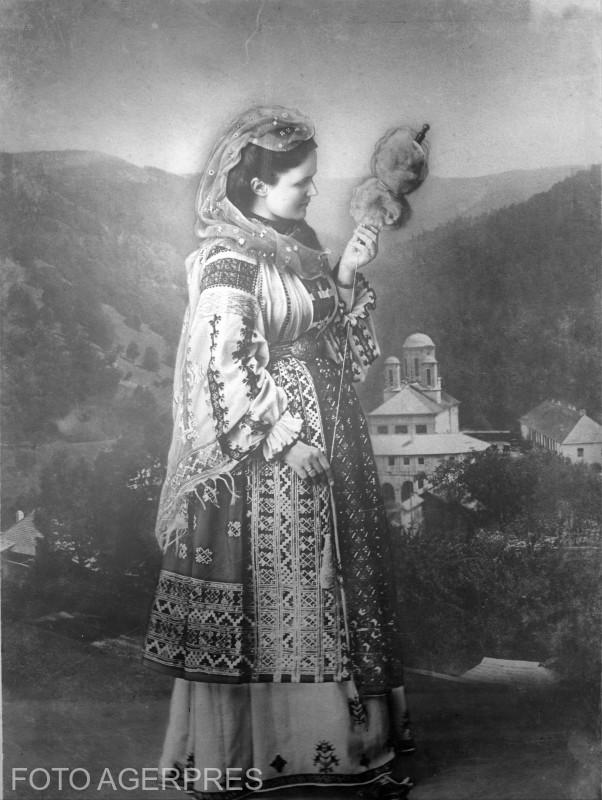 1900 - Ilustrata de epoca infatisand-o pe Regina Elisabeta, in port popular romanesc; in fundal se vede Manastirea Sinaia.