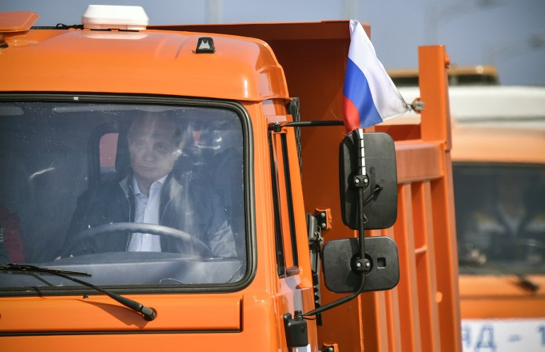 Russian President Vladimir Putin drives a construction truck across the new 19 kilometres (12 miles) road-and-rail Crimean Bridge over the Kerch Strait linking mainland Russia to Moscow-annexed Crimea during the opening ceremony on May 15, 2018. Vladimir Putin inaugurated the bridge consisting of parallel road and railway sections that link southern Russia to the Crimean peninsula which was annexed from Ukraine in 2014, a highly symbolic project he has personally championed. Built at a cost of 228 billion rubles ($3.69 billion), the new structure connects the southern Krasnodar region with the Crimean city of Kerch, spanning a strait between the Black Sea and the Azov Sea. / AFP PHOTO / POOL / Alexander NEMENOV